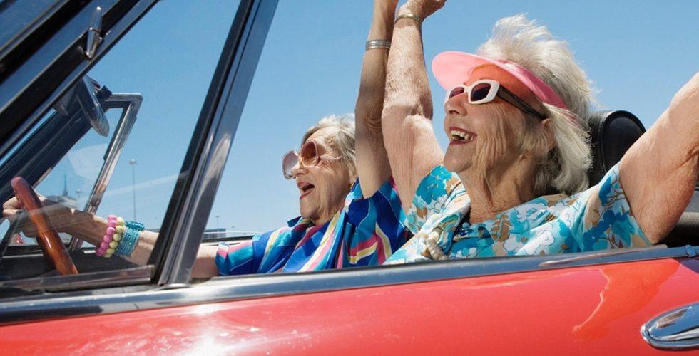Две пожилые женщины едут в открытом автомобиле-кабриолете и радуются жизни.Одна из них за рулем.