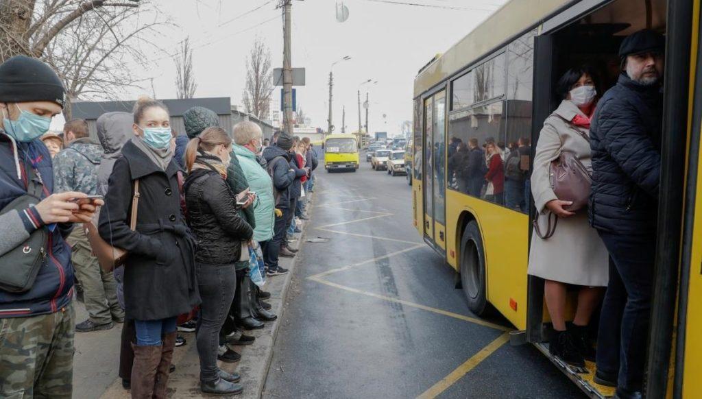Люди на остановке и в автобусе в защитных масках