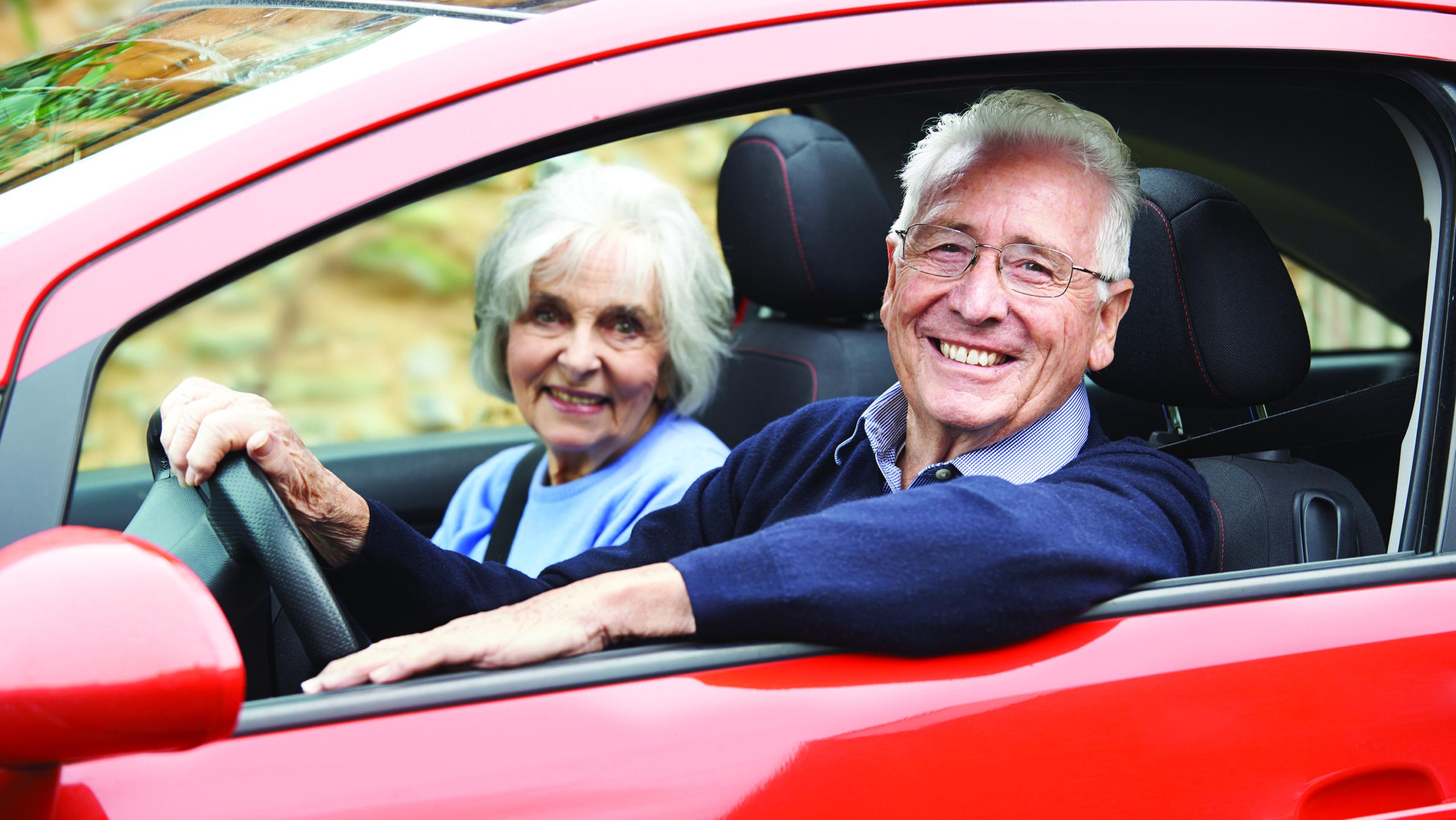 Пожилой водитель за рулем автомобиля со своей спутницей