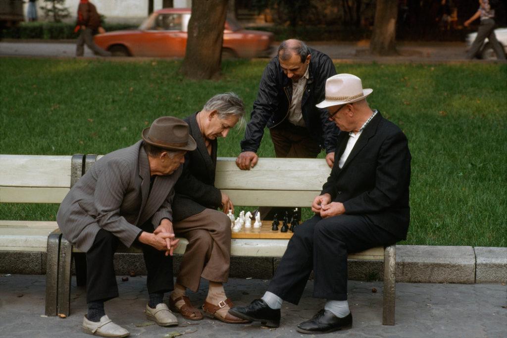 Пожилые люди сидят на скамейке и играют в шахматы.