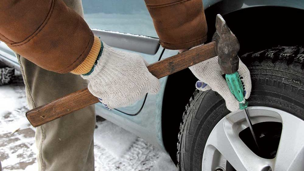 Обстукивание примерзших тормозных барабанов и суппортов с помощью молотка и большой отвертки